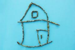 Litet hus av pinnar på en blå bakgrund, begrepp royaltyfri bild