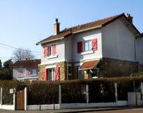 Litet hus med röda slutare Royaltyfri Foto