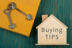 litet hus med text ' köpande tips' , bok och tangent på det blåa träskrivbordet royaltyfria bilder