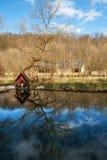 Litet hus på ett damm med reflexioner Fotografering för Bildbyråer
