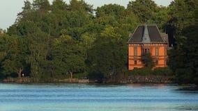Litet hus på kusten av sjön stockholm sweden lager videofilmer
