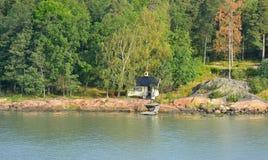 Litet hus på stenig kust av Östersjön Royaltyfri Foto