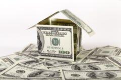 Litet hus som göras av dollarräkningar Arkivbild