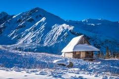 Litet hus som täckas med insnöat bergen Royaltyfri Fotografi