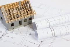 Litet hus under konstruktion och elektriska teckningar, begrepp av byggnadshemmet arkivbilder