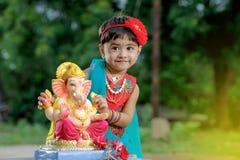 Litet indiskt flickabarn med ganesha och att be för lord, indisk ganeshfestival Arkivfoton