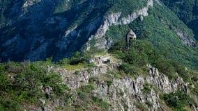 Litet kapell med berg i bakgrunden Arkivbild