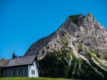 litet kristen kyrka eller kapell i berglandskap, Schweiz fjällängar arkivfoton