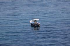 Litet lanseringsfartyg med folk, det blåa havet och himmel royaltyfri foto
