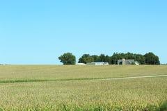 Litet lantgårdhus och en ladugård med en silo arkivbilder