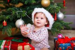 Litet le behandla som ett barn i hatt av Santa Claus på en bakgrund av julgirlanden, trädet och gåvaaskar med bandet fotografering för bildbyråer