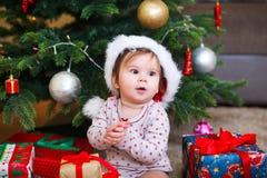 Litet le behandla som ett barn i hatt av Santa Claus på en bakgrund av julgirlanden, trädet och gåvaaskar med bandet arkivfoto