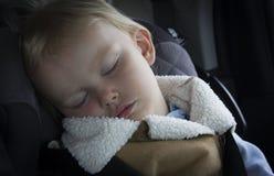 Litet liten flickalitet barn som sover i hennes bilsäte Arkivbild
