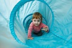 Litet litet barn som spelar i ett tunnelrör Royaltyfria Bilder