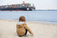 Litet litet barnpojkesammanträde på sandstranden och se på containe Royaltyfria Bilder