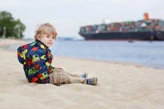 Litet litet barnpojkesammanträde på sandstranden och se på containe Royaltyfri Fotografi