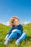Litet lockigt flickasammanträde på gräs Royaltyfri Foto