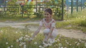 Litet lockigt och mer flicka som blåser maskrosen och mer ultrarapidvideo liten flicka som spelar med blommamaskrosor in lager videofilmer