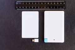 Litet mini- format för maktbank på kreditkorten och linjaler på svarta lodisar Royaltyfri Bild