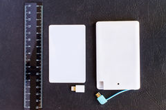 Litet mini- format för maktbank på kreditkorten och linjaler på svarta lodisar Arkivfoto