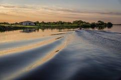 Litet motoriskt fartyg på solnedgången på Rio Paraguay Royaltyfri Foto