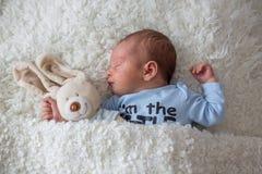 Litet nyfött behandla som ett barn att sova, behandla som ett barn med den överilade scinen Arkivbilder