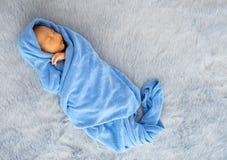 Litet nyfött behandla som ett barn slås in med den blåa handduken, och behandla som ett barn sover på grå matta royaltyfria foton