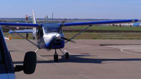 Litet privat flygplan med ett roterande propelleranseende på flygplanparkeringen på ett litet flygfält
