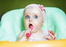 Litet roligt barn med rosa färgskeden Arkivfoto
