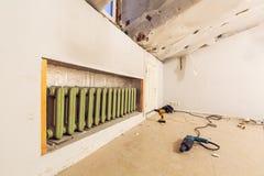 Litet rum med centralvärme med att värma järn- element- och konstruktionshjälpmedel på golvet är i apartmen royaltyfria foton