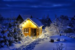 Litet ryskt trähus-Banya efter häftiga snöstormen i skymning arkivbild