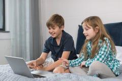 Litet sammanträde för dator för pojke- och flickabruksbärbar dator på säng i sovrummet, broderAnd Sister Surfing internet Royaltyfri Foto