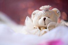 Litet sammanträde för dockan för nallebjörnen på vit matta med suddighetsrosa färger färgar bokehbakgrund royaltyfri foto