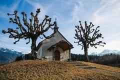 Litet schweiziskt kapell i vinter med berg i bakgrunden fotografering för bildbyråer