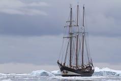 Litet seglingskepp i Antarktisvatten mellan isisflak och is Arkivbild