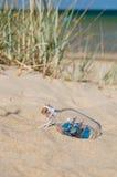 Litet skepp i glasflaskan som ligger på stranden Royaltyfria Foton