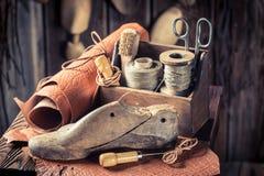 Litet skomakareseminarium med skor, trådar och hjälpmedel Royaltyfri Fotografi