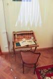 Litet skrivbord för exponering med en bok Arkivbild