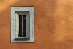 Litet smalt fönster i en gammal återställd byggnad med den nya målade fasaden Royaltyfria Bilder