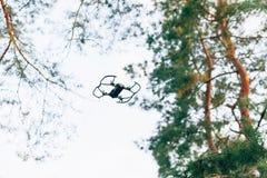 Litet smart surrquadrocopterflyg på vit himmel och gröna träd royaltyfri bild
