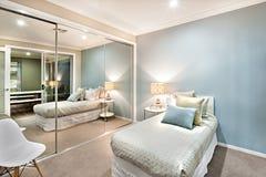 Litet sovrum med kuddar på en enkel säng arkivfoton