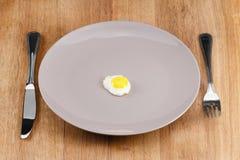 Litet stekt ägg på en platta royaltyfria foton