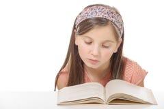 Litet studentflickastudera och läsebok på skolan Royaltyfri Foto