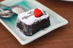 Litet stycke av chokladkakan med sidosikt för florsocker och för jordgubbe överst, på den fyrkantiga plattan på den wood tabellen Royaltyfri Fotografi