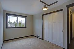 Litet tomt sovrum med byggt i garderob royaltyfri foto