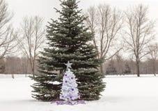 Litet träd för vit jul med lilor och silvergarneringar som står i snö Arkivbilder