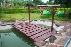 Litet trädgårds- damm med träbron i sommar fotografering för bildbyråer