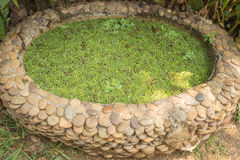 Litet trädgårds- damm som göras av grusstenar Arkivfoto
