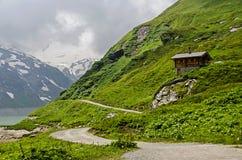 Litet trevligt hus som är högt i bergen av fjällängarna i kaprun Arkivbild