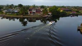 Litet turist- fartyg som långsamt seglar i lugna djupblått kanalflodvatten i tropiskt landskap, i att bedöva skottet för antenn 4 stock video
